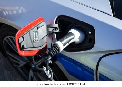 Electric vehicle is plugged into electricity. Battery in car and auto is recharged. Electric green energy as source of energy for transportation