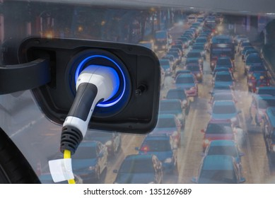 Electric vehicle , Smart car , Air pollution and reduce greenhouse gas emissions concept. Double exposure of charging Electric car with power cable supply plugged in and city night light view.