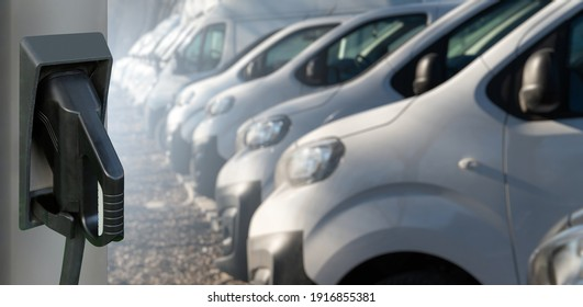 Electric vehicles charging station on a background of a row of vans. Concept