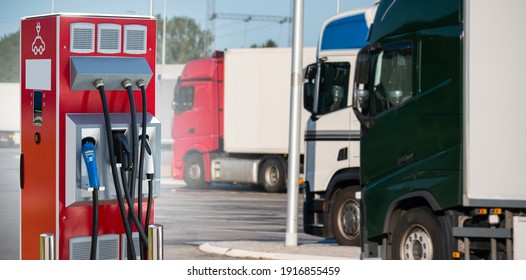 Electric vehicles charging station on a background of a row of trucks. Concept