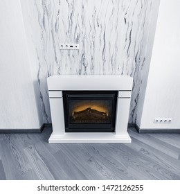 Electric warm cozy fireplace with the man-made wood and light in it.
