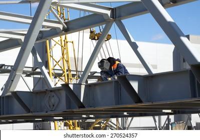Electric welding worker welds metal structures in the construction of industrial facilities