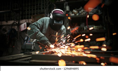 Electric wheel grinding on steel structure in factory. Metal works.