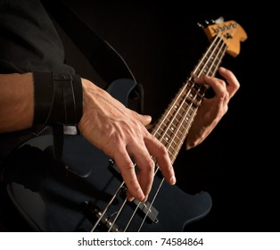 electrical bass guitar in male hands, black background