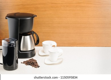 Electrical coffee machine with stainless steel coffee pot and handful coffee beans on the wood and marble background. Copy space.
