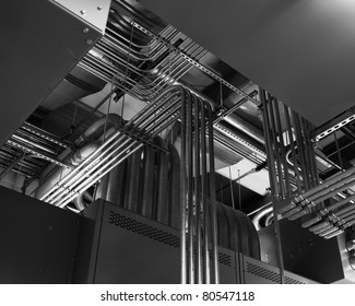 Electrical conduits run along a ceiling in a switchgear room.