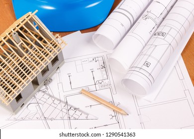 Electrical diagrams, accessories for engineer jobs and house under construction lying on desk, concept of building home