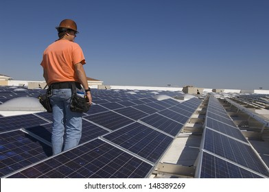 Electrical engineer among solar panels at solar power plant