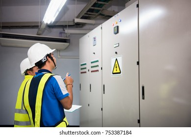 Electrical engineer in the control room and recording in operation of power in the plant for production process, routine daily record. Focusing on foreground people learning concept.