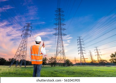 Electrical engineer with high voltage electricity pylon at sunrise background
