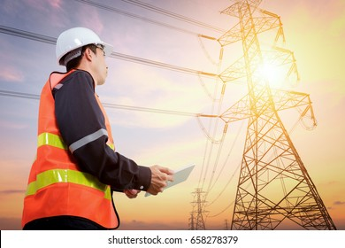 Electrical engineer with high voltage electricity pylon at sunset background