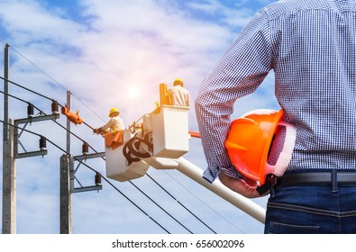 Electrical engineer holding safety helmet with electricians working on electric power pole with  bucket hydraulic lifting platform