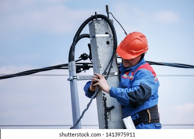 electrical engineer performs wiring on a high pole standing on the stairs. high-rise electrical work. podkluchenie house to the power lines