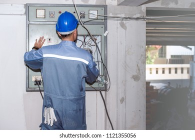 Electrical engineer put on a blue helmet does not put gloves on inspect damaged circuit breaker center with carelessness. Gloves in pants pocket