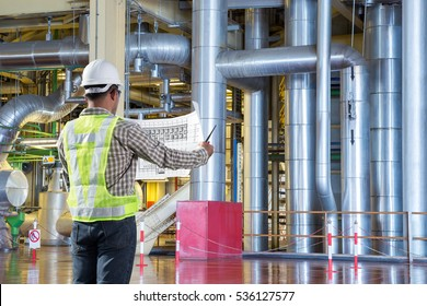 Electrical engineer reading drawing diagram for maintenance at thermal power plant factory