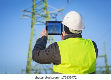 Electrical Engineer with tablet PC near High voltage tower
