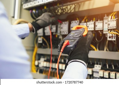 Electrical engineer using digital multi-meter to check current voltage at circuit breaker in main distribution board.