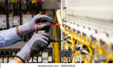 Electrical engineer using digital multi-meter measuring equipment to checking electric current voltage at circuit breaker and cable wiring system in main power distribution board.