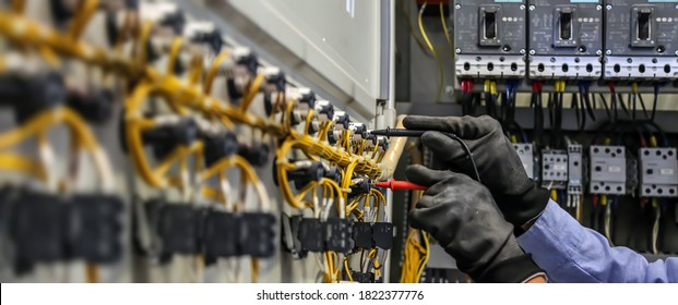 Electrical engineer using measuring equipment to checking electric current voltage at circuit breaker and cable wiring system for maintenance in main power distribution board.