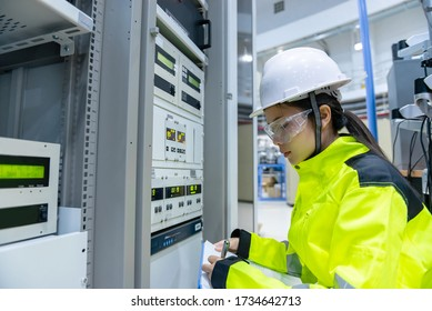 Electrical engineer woman checking voltage at the Power Distribution Cabinet in the control room,preventive maintenance Yearly,Thailand Electrician working at company