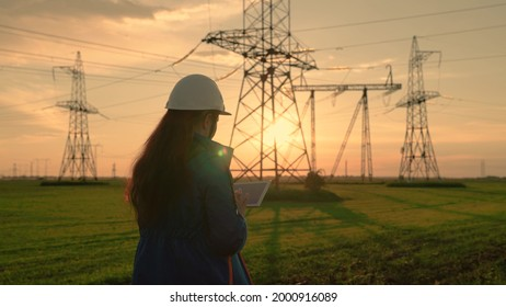 An electrical engineer, woman working with computer tablet, works with electricity next to an electric tower. Industry of energy business technologies. An electrical engineer works on digital tablet