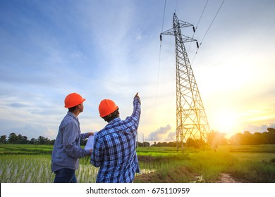 Electrical engineer working. Electrician holding blueprint at high voltage power pylon against blue sky