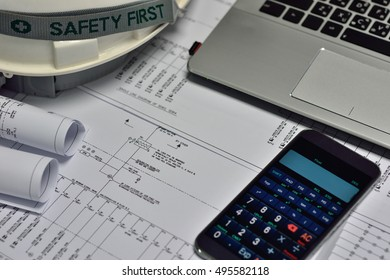 Electrical engineering drawings and digital multimeter with safety helmet, electri calculator, note book or engineering electrical desk.