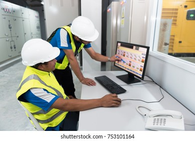 Electrical engineering with inspector while training and recording in operation of power in the plant for production process, routine daily record. Focusing on foreground people learning concept.