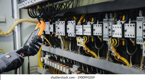 Electrical engineers test electrical installations and wiring on protective relays, measuring them with a multimeter.