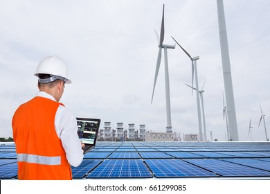 Electrical engineers working at wind turbine power generator station with solar panel, energy concept