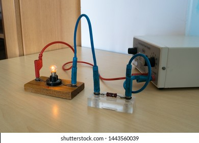Electrical experiment in physics laboratory. Electrical circuit with resistor and light bulb.
