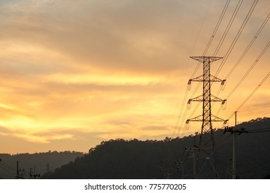 Electrical grid transmission power lines with wind turbines and sunset, and blue sky. high voltage pole in countryside