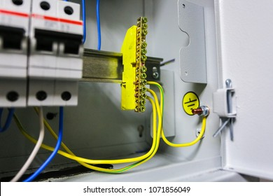 Electrical ground wires is connected to ground copper bar or earth bonding bar in metal electric breaker box with electrical circuit breakers and electrical grounding sign near ground bolt