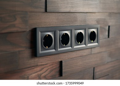 Electrical household switches and sockets close up. Minimalist interior design. Stylish bedroom and living room. Wooden bricks wall in a designer minimalist room. Wooden parquet room. Scandinavian