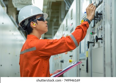 Electrical and Instrument technician checking electrical parameter of power electric generator in switch gear room before sync power to the main system.