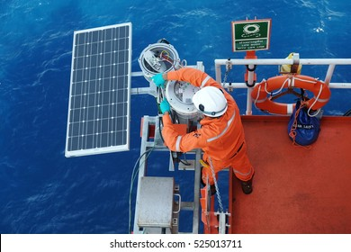 Electrical and Instrument Technician is inspection on lighting of navigation aid system at oil and gas wellhead remote platform, Inspector work.solar energy panel photovoltaics module
