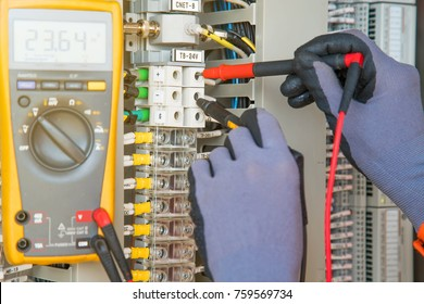 Electrical and instrument technician measuring voltage at electric terminal for troubleshooting electrical system of oil and gas control process, A man using digital multi meter measure volt.