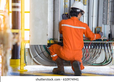 Electrical and instrument technician troubleshooting on programmable logic controller of oil and gas production system, offshore oil rig worker.