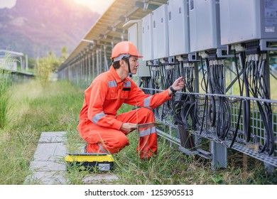 Electrical and instrument technician use touchpad for guide to maintenance electric system at electric solar plant