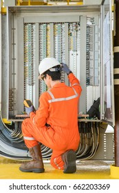 Electrical and instrument technician using digital multi meter measuring electric voltage on programmable logic controller ( PLC ) junction box at offshore oil and gas processing platform.