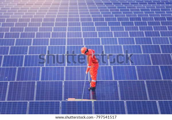 Electrical and instrument technician wash and cleaning solar panel at solar plant field