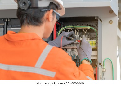 Electrical and instrument technician wiring cable at terminal and junction box, an oil rig worker maintenance electric system on offshore platform.