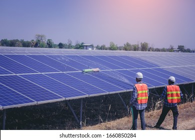 Electrical, instrument technician worker washing and cleaning solar panels at solar electrical system field