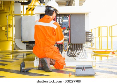 Electrical and instrument worker inspect and checking voltage and current of electric system at oil and gas platform for preventive maintenance, offshore oil rig electrician occupation.