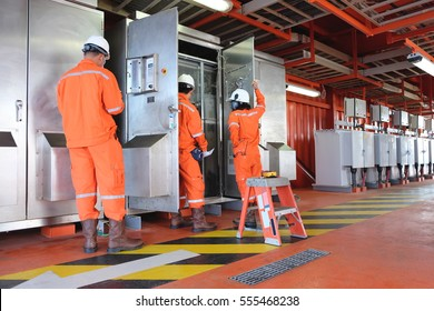 Electrical and Instrument working on direct current power distribution system on offshore oil and gas platform, Electrician measuring voltage and logging data in sheet, electrical service at offshore.