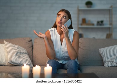 Electrical Issue. Girl Calling Electrician Service Via Mobile Phone Sitting On Couch In Dark Room Lit By Candles. Selective Focus