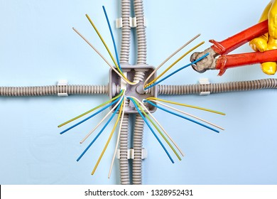 Electrical junction box in the process of installation, electrical conduits terminate at the sides and cables pass through or joined inside the box.