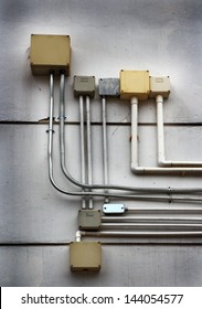 electrical junction boxes and tube against a concrete block wall
