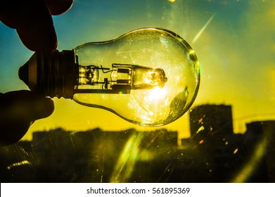 electrical light bulb in hand on blue sky background. sunny day light. Hand holding light bulb on a background sky and sun. An abstract idea on the topic of electricity of alternative solar energy.