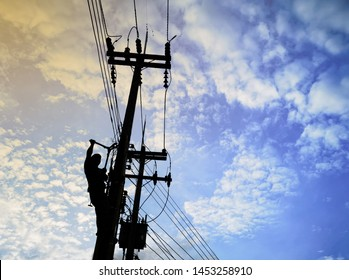 Electrical lineman working on high voltage pole , put safety equipment in sky blackground.